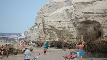 Muchos bañistas buscan la sombra y de paso contemplan el arte del mar sobre la piedra.