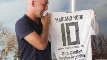 Hood muestra sonriente la camiseta que le regaló el club.