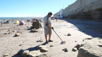 El turista busca tesoros en la playa con un detector de metales