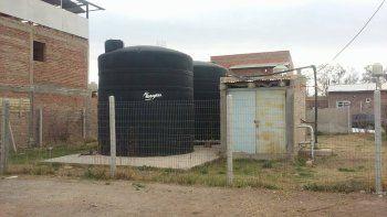 El agua se extrae de un pozo y se almacena en dos grandes tanques.