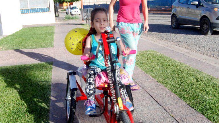 Carmela disfruta de su tricicleta, impulsada con la fuerza de sus brazos.