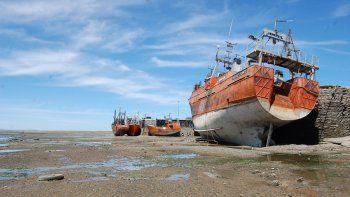 Parece un cementerio de barcos, pero simplemente se trata de la bajamar en el muelle de los pescadores.