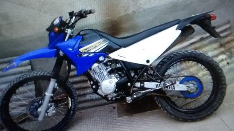 La moto es azul y blanca y no tiene la patente a la vista.