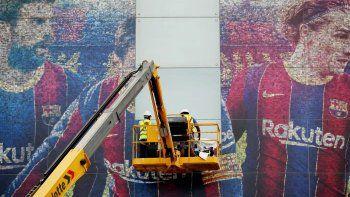 Operarios contratados por el Barsa, arrancando la imagen de Messi del Camp Nou.