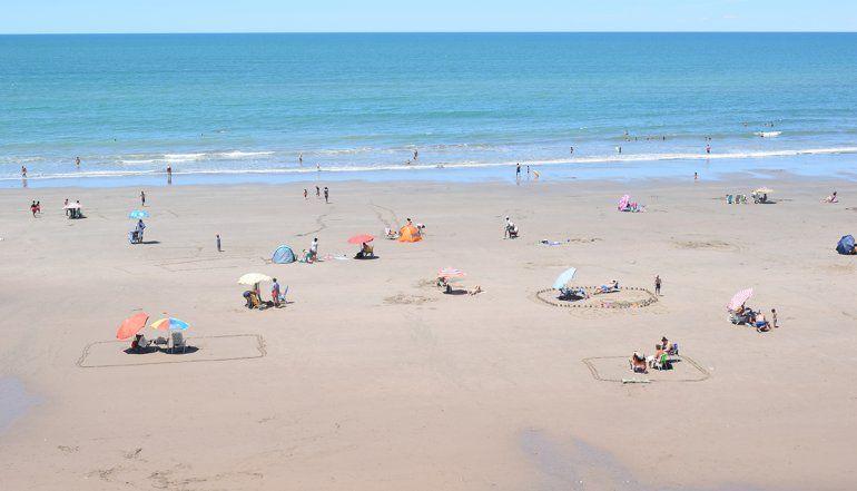 Veraneantes marcan su sector de playa para mantener la distancia sugerida para frenar el Covid.