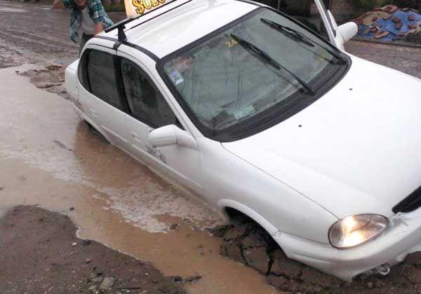 Por esquivar un pozo, un taxi terminó dentro de una zanja
